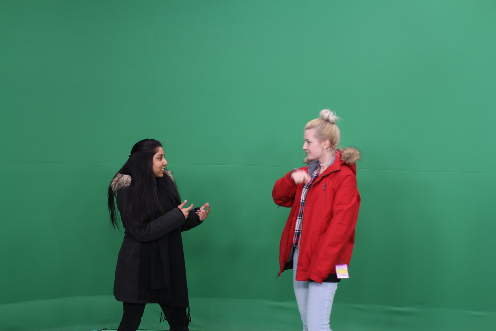 Celeena and a friend in front of a green screen